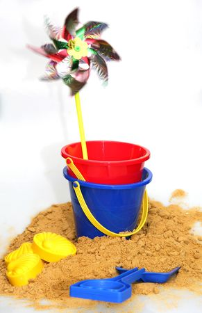 A holiday image of buckets and spades and a windmill with sand from a beach