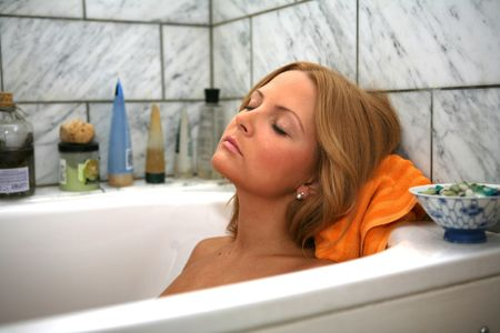 A Pretty Girl Relaxes in the Bath early one morning Stock Photo