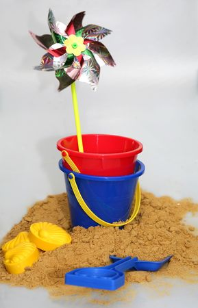 A rotating childs windmill, buckets and spades recalling seaside fun. Stock Photo