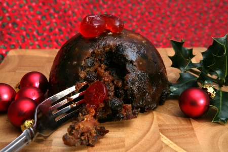 A tasty Christmas Pudding with Cherries and Baubles Stock Photo