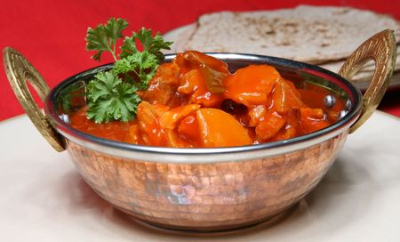 A tasty meal of Chicken Curry served in a Balti dish or Karahi, with chapattis Stock Photo