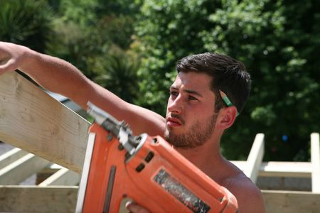 A construction worker uses a nail gun to secure roof timbers
