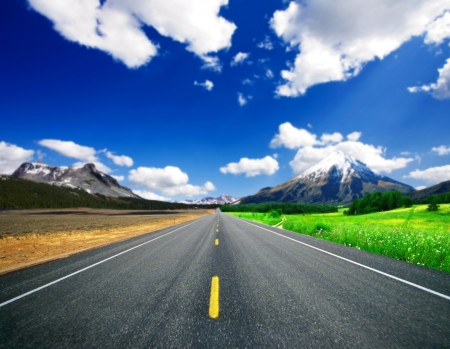 asphalt road through the green field and the arid and clouds on blue sky.