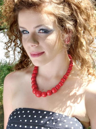 Curly woman with red jewellery photo