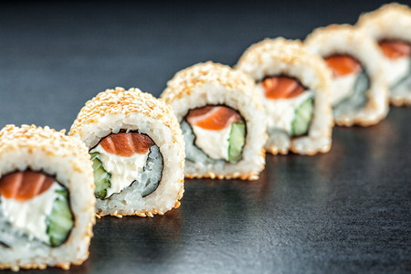 California Sushi maki with salmon and philadelphia cheese on the dark background , focus on one roll. Soft focus