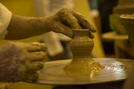 Hands working on pottery wheel, Clay modeling