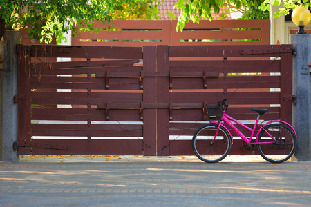 A Pink Bicycle with Wood Gate on Background