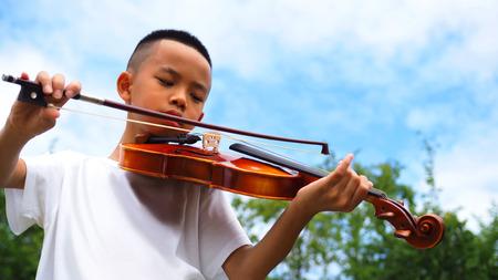 Asiatischer Junge , der Violine mit Hintergrund des blauen Himmels spielt Standard-Bild - 92849032