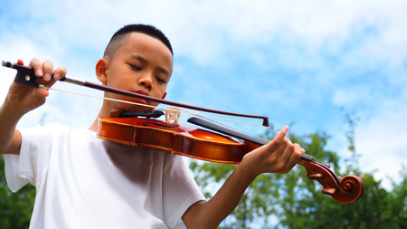 Asian boy playing violin with blue sky background. Banque d'images