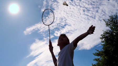 Asian boy practicing his badminton serve in a hot sunny day.(selected focus) Stock Photo