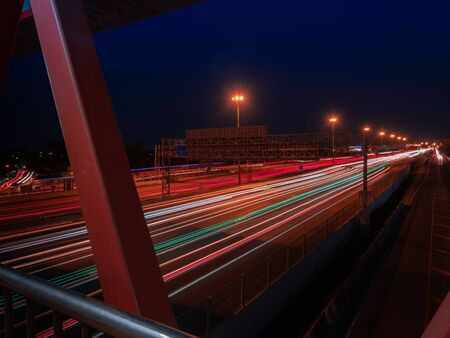 Light trails of the cars on a motorway at night. Seeing motion blurred of the car headlights and taillights on the multiple lanes.