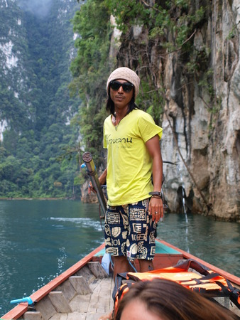 kao sok: Suratthani, Thailand - March 9, 2012: Fisherman control a longtail boat on lake Cheow Lan, Khao Sok National Park, Suratthani province - Thailand.