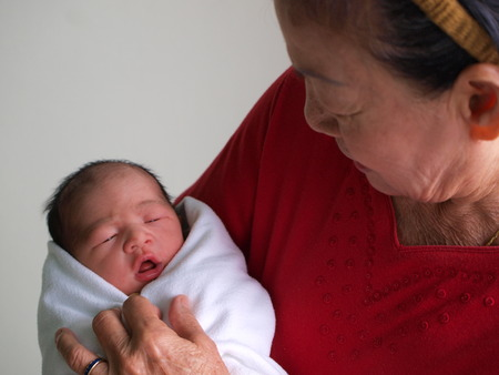 Newborn baby in the hand of his grandmother.