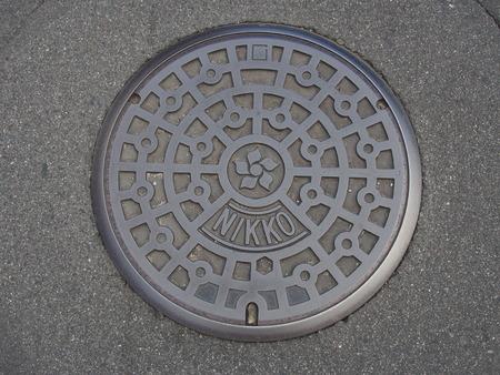 Manhole drain cover on the street at Nikko, Japan photo