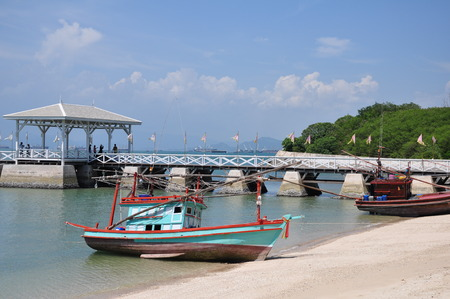 Thai fishing wooden boat at the beach and Asdang Bridge as a background. photo