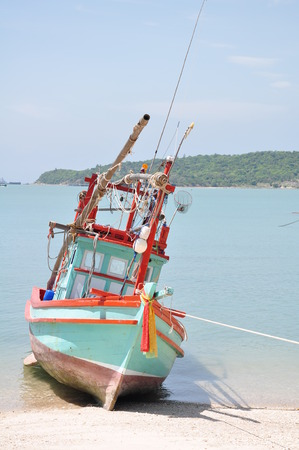 Thai fishing wooden boat at the beach photo