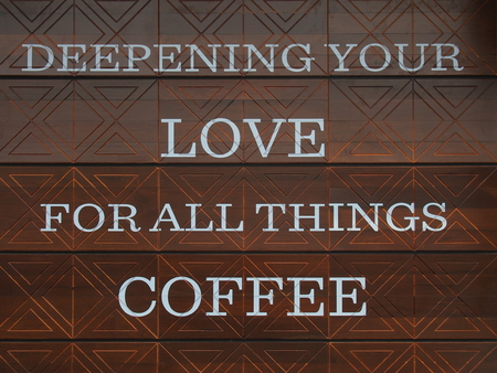Deepening Your Love For All Things Coffee  quote on wooden wall for background photo
