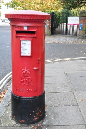 pillar box: red vintage british postbox on the sidewalk