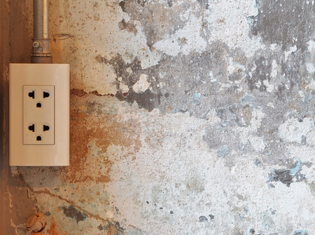 Electric plug on grunge cement wall background. For copy space. photo