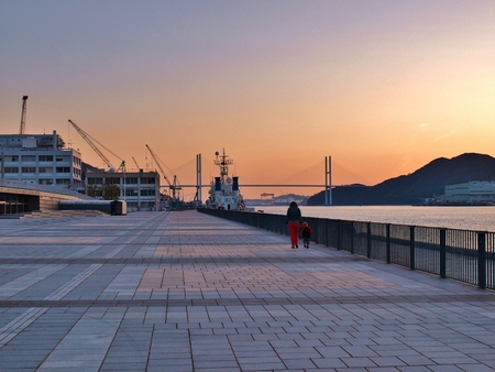 seafront: women and her child walk at seafront street with sunset lights in the evening at Nagasaki, Japan.