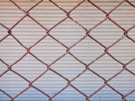 shutter door: Old rusty iron net on shutter door background.