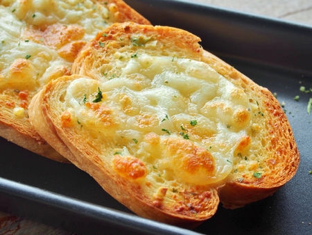 Close-up of a dish of garlic bread with cheese.