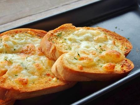 ajo: Primer plano de un plato de pan de ajo con queso.