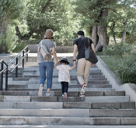 Young family - father, mother and their daughter holding hand and walking up stairs in the park, soft tone.