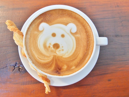 Latte Coffee art Dog Face and biscuit stick on the wooden desk. Stok Fotoğraf