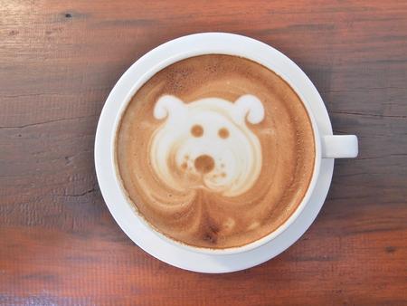 """filiżanka kawy: Kawa Latte Art """"Dog Face"""" na drewnianym biurku. Zdjęcie Seryjne"""