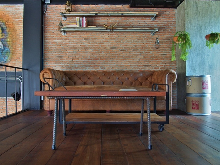 Retro living room interior with leather sofa and wooden sofa table in front of brick wall. Stock Photo
