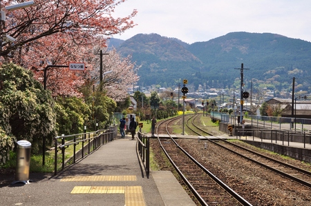 railway at Yufuin train station with cherry blossom sakura and mountain background in Oita, Japan. Tourists enjoy beautiful scenery.
