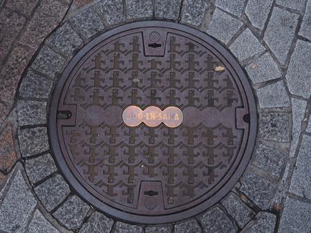 manhole cover: TOKYO, JAPAN - NOVEMBER 15, 2015: The funny marking on manhole cover in Shibuya, Tokyo, Japan.