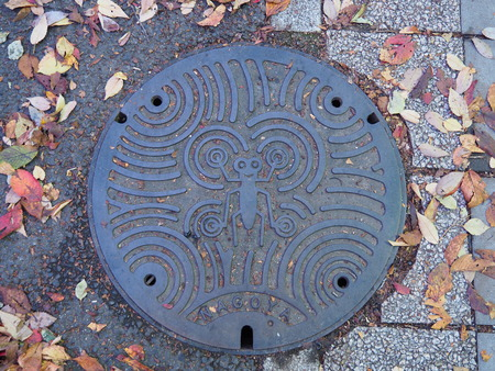 NAGOYA, JAPAN - NOVEMBER 16, 2015: A manhole cover in Nagoya, Aichi Prefecture, Japan. Abstract symbol engraved on to a manhole along a street in Nagoya city. Editorial