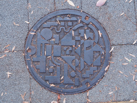 manhole cover: NAGOYA, JAPAN - NOVEMBER 16, 2015: A manhole cover in Nagoya, Aichi Prefecture, Japan. Abstract geometric symbols engraved on to a manhole along a street in Nagoya city.