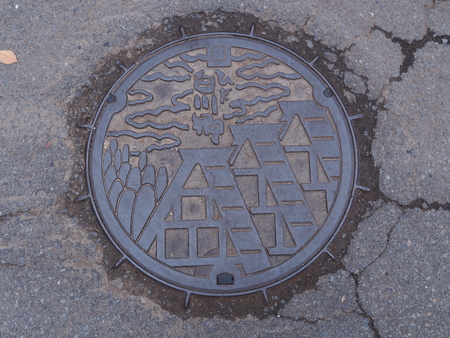 manhole cover: GIFU, JAPAN - NOVEMBER 17, 2015: A manhole cover of Shirakawago village, Gifu Prefecture, Japan. The Gassho Style houses engraved on to a manhole cover as a symbol of an important villages landmark. Editorial