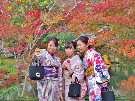 KYOTO, JAPAN - NOVEMBER 21, 2015: Three young women wear a traditional dress called Kimono taking selfie with mobile phone with red leaves background at Eikan-do temple in Kyoto, Japan. Stok Fotoğraf