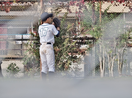 left hand: Young Japanese baseball player no.17 pitching by left hand. This photo was taken through a wire mesh fence.