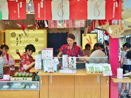 TOKYO, JAPAN - JULY 16, 2014: Japanese women dressed in traditional dress are selling dessert and beverage to customers at Nakamise Dori, one of the oldest shopping streets in Tokyo, Japan.