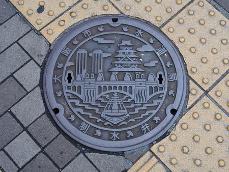 manhole cover: OSAKA, JAPAN - JUNE 08, 2016: A manhole cover in Osaka, Japan. A ship on Dotonbori canal and Osaka castle engraved on to a manhole cover as a symbol of an important citys landmark.