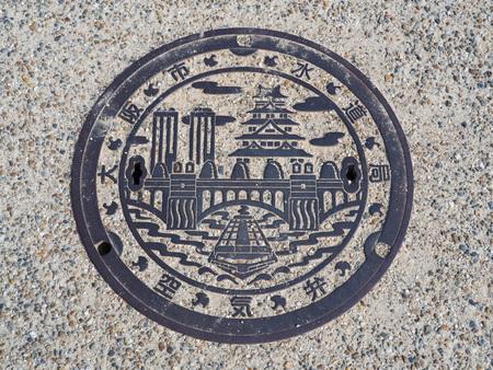 manhole cover: OSAKA, JAPAN - JUNE 09, 2016: A manhole cover in Osaka, Japan. A ship on Dotonbori canal and Osaka castle engraved on to a manhole cover as a symbol of an important citys landmark.
