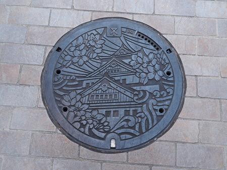 manhole cover: OSAKA, JAPAN - JUNE 08, 2016: A manhole cover in Osaka, Japan. The Osaka castle and sakura engraved on to a manhole cover as a symbol of an important citys landmark.