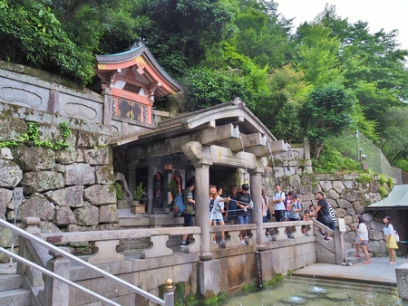 longevity: KYOTO, JAPAN - JUNE 08, 2016: Many people collecting water from the Otowa-no-taki waterfall at Kiyomizu-dera temple. Visitors believe that water have enhance health, longevity, and success in studies.