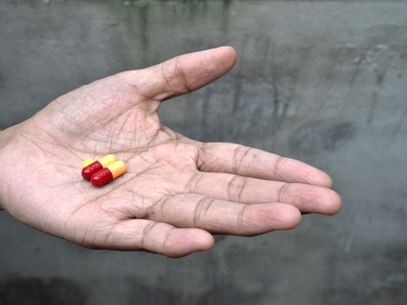 unhealthiness: elder hand holding or offering pills, concept of healthy and medical.