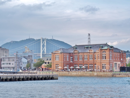 Fukuoka, Japan - July 17, 2016: Old Moji Customs Office, built in 1912 at Moji port in Kitakyushu, Fukuoka , Japan. In the building has a coffee shop and art gallery. Kanmonkyo Bridge on background.