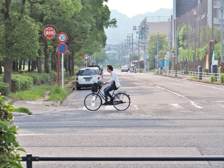 Hiroshima, Japan - July 18, 2016: Unidentified man cycling on the street in Hiroshima city, Hiroshima Prefecture, Japan.