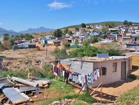 Informal settlement - Enkanini with mountain and blue sky on the outskirts of Stellenbosch, Western Cape province, South Africa. Many shacks in Enkanini have solar panels for access to electricity. Stock Photo