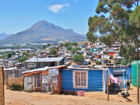 Informal settlement - Enkanini with mountain and blue sky on the outskirts of Stellenbosch, Western Cape province, South Africa. Many shacks in Enkanini have solar panels for access to electricity. Banco de Imagens