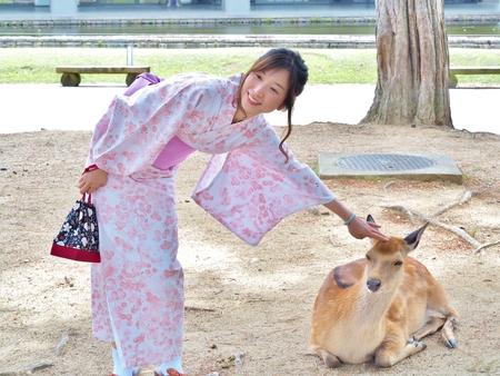 Nara, Japan - June 6,2016: Unidentified beautiful woman in Japanese traditional dress called Yukata play with deer at Nara Park. Nara Park is a large park in central Nara, home of freely roaming deer. Editorial