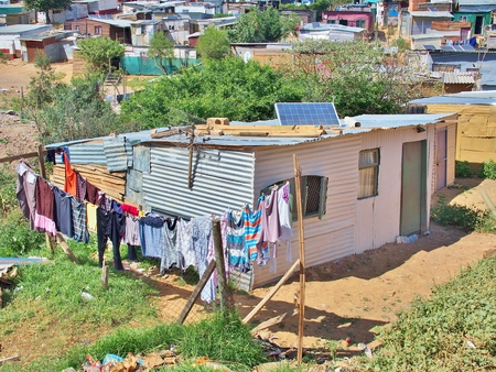 Solar panels on the roof of shack at Informal settlement - Enkanini, on the outskirts of Stellenbosch, Western Cape, South Africa. Many shacks in Enkanini have solar panels for access to electricity. Stock Photo
